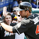 Miami Marlins' Garrett Jones, right, returns to high-fives in the dugout after hitting a solo home run during the fifth inning of a baseball game against the Philadelphia Phillies, Sunday, April 13, 2014, in Philadelphia The Associated Press