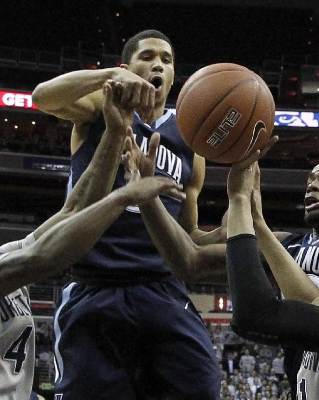 Georgetown guard D'Vauntes Smith-Rivera, left, Villanova guard Josh Hart, Villanova guard James Bell, and Georgetown guard Stephen Domingo, battle for a rebound, during the first half of an NCAA college basketball game, Monday, Jan. 27, 2014, in Washington. Villanova won 65-60
