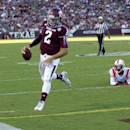 Texas A&M quarterback Johnny Manziel (2) rushes for a 7 yard touchdown as he avoids the tackle of SMU defensive back Kenneth Acker (21) during the first quarter of an NCAA college football game Saturday, Sept. 14, 2013, in College Station, Texas. (AP Photo/Bob Levey)