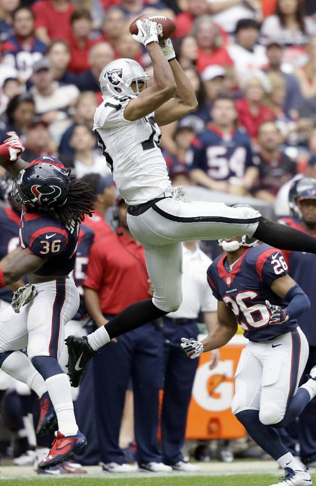 Oakland Raiders' Andre Holmes leaps to catch a pass over Houston Texans' D.J. Swearinger (36) and Brandon Harris (26) during the first half of an NFL football game Sunday, Nov. 17, 2013, in Houston