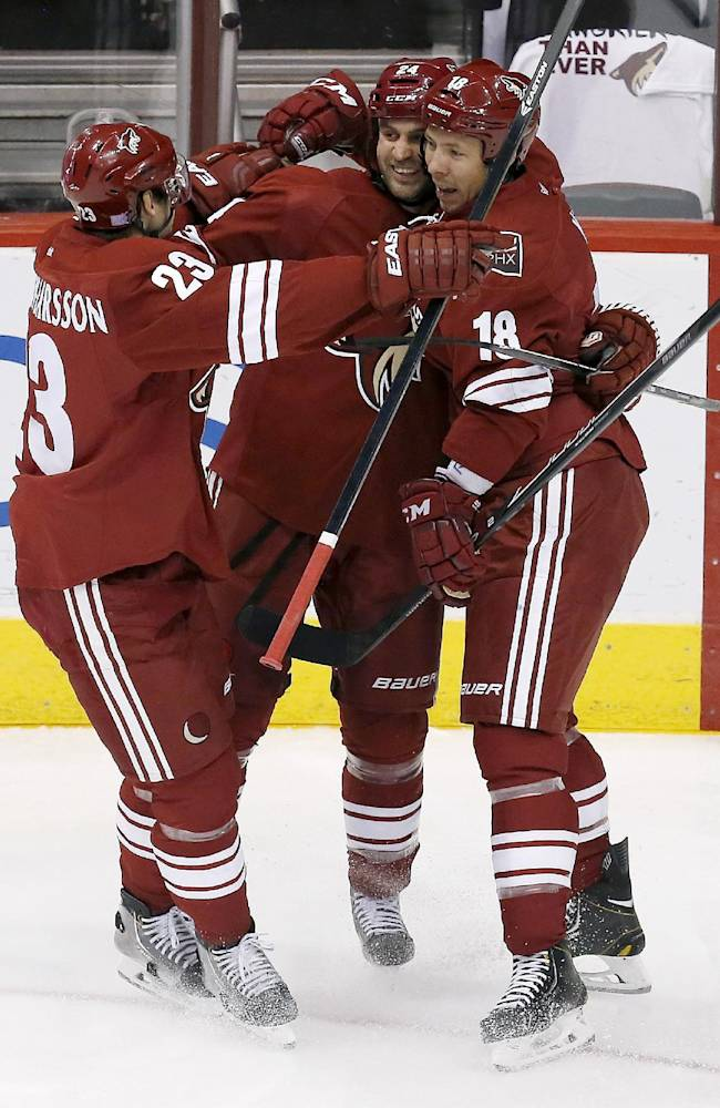 Phoenix Coyotes' Kyle Chipchura (24) celebrates his goal against the New York Rangers with teammates Oliver Ekman-Larsson (23), of Sweden, and David Moss (18) in the first period during an NHL hockey game on Thursday, Oct. 3, 2013, in Glendale, Ariz