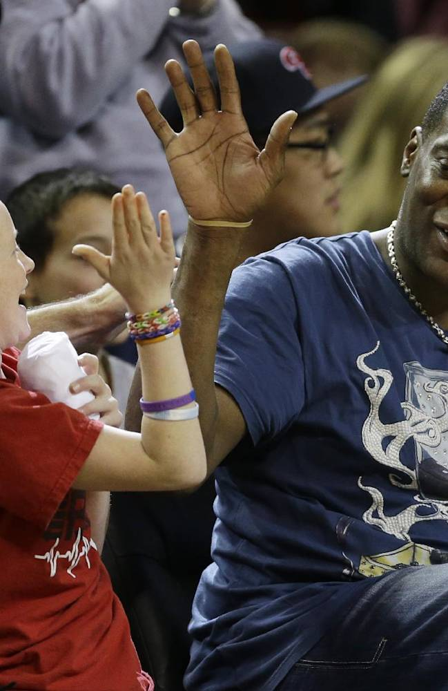 Seattle SuperSonics legend Shawn Kemp, right, hi-fives a young fan as they sit courtside at an NCAA college basketball game between Gonzaga and South Alabama, Saturday, Dec. 14, 2013, in Seattle