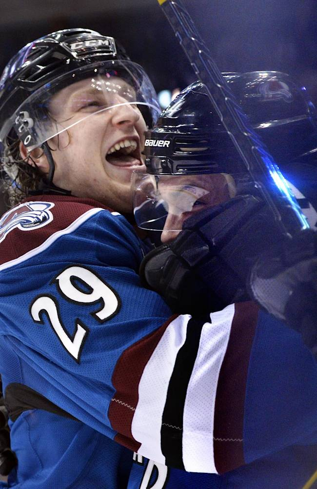Colorado Avalanche defenseman Tyson Barrie embraces Nathan MacKinnon (29) after scoring a goal to tie the game against the New York Rangers during the third period of an NHL hockey game on Thursday, April 3, 2014, in Denver. Colorado won 3-2 in an overtime shootout