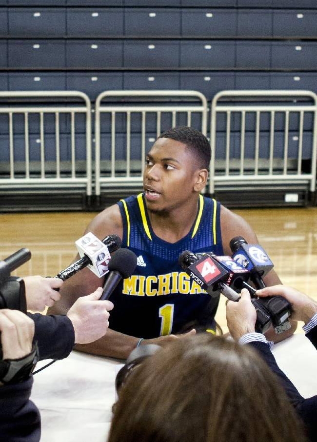 Michigan forward Glenn Robinson III, center, is surrounded by reporters during an NCAA college basketball media day Thursday, Oct. 24, 2013, in Ann Arbor, Mich