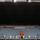 FILE - In this Tuesday, Sept. 30, 2014, file photo, a steward stands amidst empty seats in a stadium devoid of fans during the Group E Champions League match between CSKA Moscow and Bayern Munich at Arena Khimki stadium in Moscow. CSKA were sanctioned by