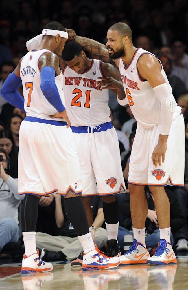 New York Knicks' Tyson Chandler, right, is helped up by Iman Shumpert (21) after injuring his knee as Carmelo Anthony watches during the first quarter of an NBA basketball game against the Charlotte Bobcats on Tuesday, Nov. 5, 2013, at Madison Square Garden in New York