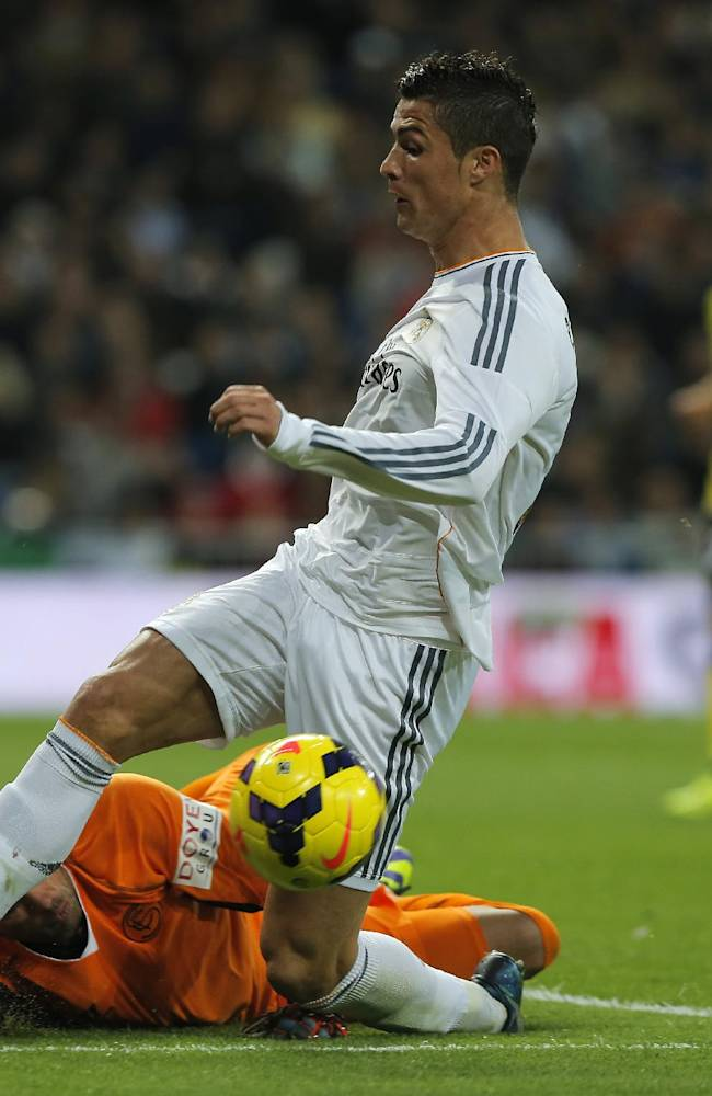 Real Madrid's Cristiano Ronaldo from Portugal, top, in action with Sevilla's goalkeeper Beto, from Portugal, bottom, during a Spanish La Liga soccer match between Real Madrid and Sevilla at the Santiago Bernabeu stadium in Madrid, Spain, Wednesday Oct. 30, 2013
