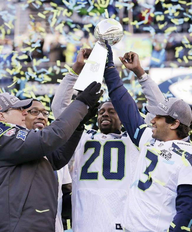 Seattle Seahawks team owner Paul Allen, left, holds up the Vince Lombardi Trophy with Russell Wilson (3) as Korey Toomer and Jeremy Lane (20) react at a rally following a parade for the NFL football Super Bowl XLVIII champions on Wednesday, Feb. 5, 2014, in Seattle. The Seahawks defeated the Denver Broncos on Sunday