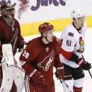 Arizona Coyotes' Michael Stone (26) and Ottawa Senators' Mark Stone (61), who are brothers, skate next to one another in front of Coyotes goalie Mike Smith (41) during the third period of an NHL hockey game Saturday, Jan. 10, 2015, in Glendale, Ariz. The