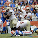 Florida State quarterback Jameis Winston (5) passes the ball as his offensive line goes to work on Florida during the first half of an NCAA college football game Saturday, Nov. 30, 2013 in Gainesville, Fla. Florida State defeated Florida 37-7. (AP Photo/Phil Sandlin)