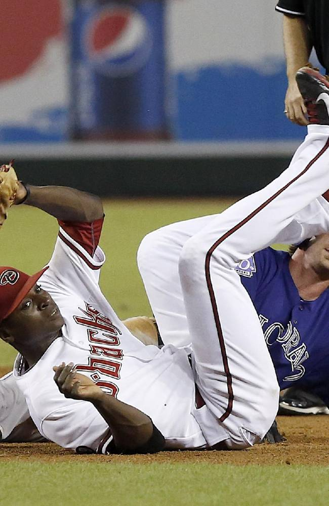 Arizona Diamondbacks' Didi Gregorius, left, lands hard onto the ground after tagging out Colorado Rockies' Charlie Blackmon, who was caught off second base after making a turn for third base on a single by Jordan Pacheco in the sixth inning of a baseball game Friday, Sept. 13, 2013, in Phoenix