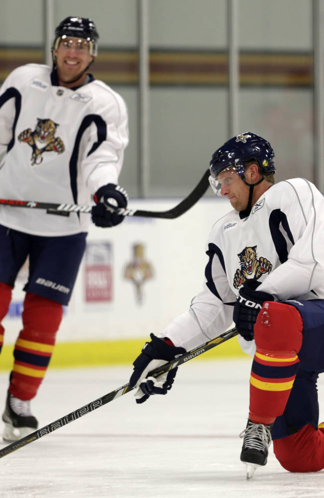 Joey Crabb, right, takes a shot as Florida Panthers center Tomas Fleischmann (14) smiles during NHL hockey training camp Thursday, Sept. 12, 2013, in Coral Springs, Fla