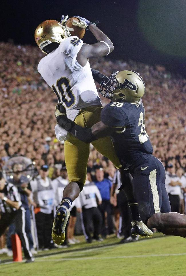 In this Sept. 14, 2013, file photo, Notre Dame wide receiver DaVaris Daniels, left, goes up over Purdue cornerback Antoine Lewis for a touchdown catch during the second half of an NCAA college football game in West Lafayette, Ind. Daniels doesn't think his 82-yard touchdown catch agaisnt Purdue was the best example of how he's improved this season. The 6-1, 200-pound wide receiver believes his 9-yard catch from Tommy Rees 2 minutes earlier was a better display of that