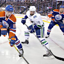 Vancouver Canucks' Chris Higgins (20) battles in the corner with Edmonton Oilers' Ryan Nugent-Hopkins (93) and Nikita Nikitin (86) during first-period NHL hockey game action in Edmonton, Alberta, Friday, Oct. 17, 2014 The Associated Press