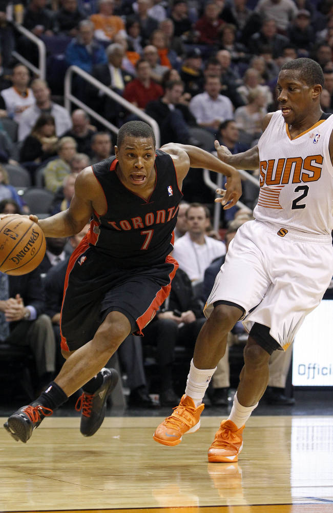 Toronto Raptors' Kyle Lowry (7) drives to the basket past the defense of Phoenix Suns' Eric Bledsoe (2) during the second half of an NBA basketball game Friday, Dec. 6, 2013, in Phoenix