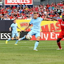 IMAGE DISTRIBUTED FOR GUINNESS INTERNATIONAL CHAMPIONS CUP - Forward Edin Dzeko (10) of Manchester City takes a shot while being defended by defender Kolo Toure (4) of Liverpool FC during the Guinness International Champions Cup on Wednesday, July 30, 201