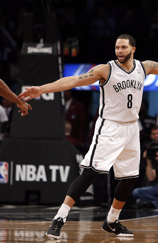 Brooklyn Nets' Deron Williams (8) reacts with teammate Alan Anderson (6) after scoring against the San Antonio Spurs during the second half of an NBA basketball game on Thursday, Feb. 6, 2014, in New York. Brooklyn won 103-89