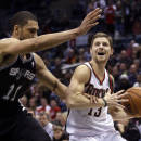 Milwaukee Bucks' Luke Ridnour(13) is fouled by San Antonio Spurs' Jeff Ayres(11) as he drives during the first half of an NBA basketball game Wednesday, Dec. 11, 2013, in Milwaukee. (AP Photo/Morry Gash)
