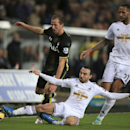 Tottenham Hotspur's Harry Kane, left, is tackled by Swansea City's Leon Britton, centre, with Swansea City's Kyle Bartley, right, during their English Premier League soccer match at the Liberty Stadium, Swansea, Sunday Dec. 14, 2014. (AP Photo / Nick Pot