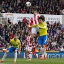 Stoke City's Peter Crouch, center, fights for the ball against Newcastle United's Fabrizio Coloccini during their English Premier League soccer match at the Britannia Stadium, Stoke, England, Saturday April 12, 2014