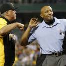 Home plate umpire C.B. Bucknor, right, ejects Pittsburgh Pirates manager Clint Hurdle who argues against him for calling Houston Astros' Jason Castro safe on a play at the plate in the eleventh inning of the baseball game on Saturday, May 18, 2013, in Pittsburgh. The run gave the Astros the margin of victory as they won 5-4. (AP Photo/Keith Srakocic)