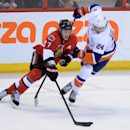 Ottawa Senators' Kyle Turris, left, fights to keep the puck away from New York Islanders' Kevin Czuczman during the second period of an NHL hockey game in Ottawa, Ontario, on Wednesday, April 2, 2014 The Associated Press