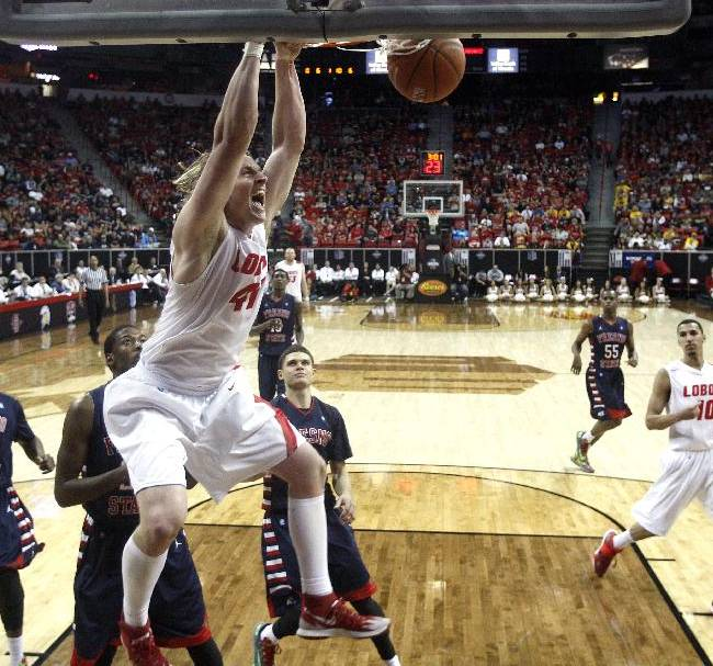 New Mexico's Cameron Bairstow dunks during the second half of an NCAA college basketball game against Fresno State in the quarterfinals of the Mountain West Conference tournament, Thursday, March 13, 2014, in Las Vegas. New Mexico defeated Fresno State 93-77