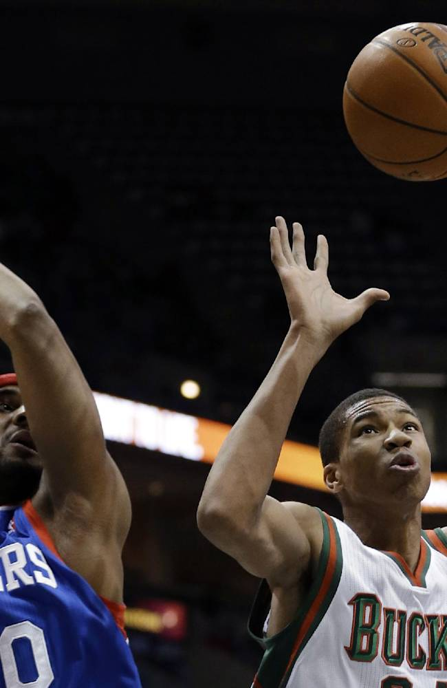 Milwaukee Bucks' Giannis Antetokounmpo and Philadelphia 76ers' Brandon Davies go after a loose ball during the first half of an NBA basketball game Saturday, Dec. 21, 2013, in Milwaukee