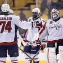 Washington Capitals defenseman John Carlson (74), right wing Joel Ward (42) and goalie Braden Holtby, right, celebrate after defeating the Boston Bruins 4-0 in an NHL hockey game in Boston, Saturday, Oct. 11, 2014 The Associated Press