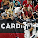 Philadelphia Eagles wide receiver Jeremy Maclin (18) gives the football to a fan after scoring a touchdown against the Arizona Cardinals as teammate Brent Celek (87) celebrates during the second half of an NFL football game Sunday, Oct. 26, 2014, in Glend