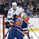San Jose Sharks' Tommy Wingels (57) and Edmonton Oilers' Boyd Gordon (27) look for the rebound in front of goalie Ben Scrivens (30) during first period of an NHL hockey game in Edmonton, Alberta, Sunday, Dec 7, 2014 The Associated Press