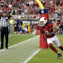 Arizona Cardinals wide receiver Larry Fitzgerald (11) runs to his bench as back judge Scott Helverson signals touchdown during the first half of the Cardinals' NFL preseason football game against the Houston Texans, Saturday, Aug. 9, 2014, in Glendale, Ar