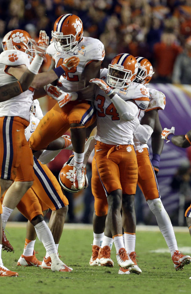 Clemson Tigers linebacker Stephone Anthony (42) celebrates with defensive end Corey Crawford (93) and linebacker Quandon Christian (34) after Anthony intercepted a pass thrown by Ohio State Buckeyes quarterback Braxton Miller during the second half of the Orange Bowl NCAA college football game, Saturday, Jan. 4, 2014, in Miami Gardens, Fla. Clemson defeated Ohio State 40-35. (AP Photo/Lynne Sladky)