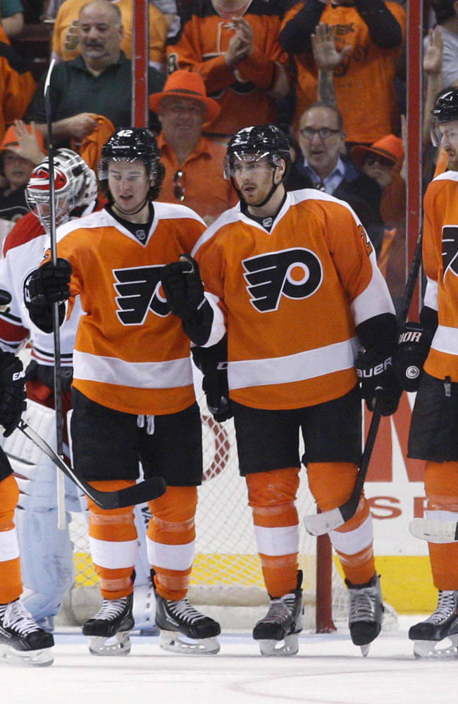 Philadelphia Flyers' Matt Read, center right, celebrates his goal on Carolina Hurricanes' Anton Khudobin, behind, with Mark Streit, left, of Switzerland; Jason Akeson, center left; and Sean Couturier, right, during the first period of an NHL hockey game, Sunday, April 13, 2014, in Philadelphia