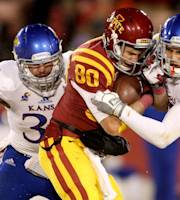 Iowa State wide receiver Justin Coleman (80) is wrapped up by Kansas linebacker Ben Heeney (31) and Kansas linebacker Jake Love (57) after catching a pass during the first half of an NCAA college football game in Ames, Iowa, Saturday Nov. 23, 2013. (AP Photo/Justin Hayworth)