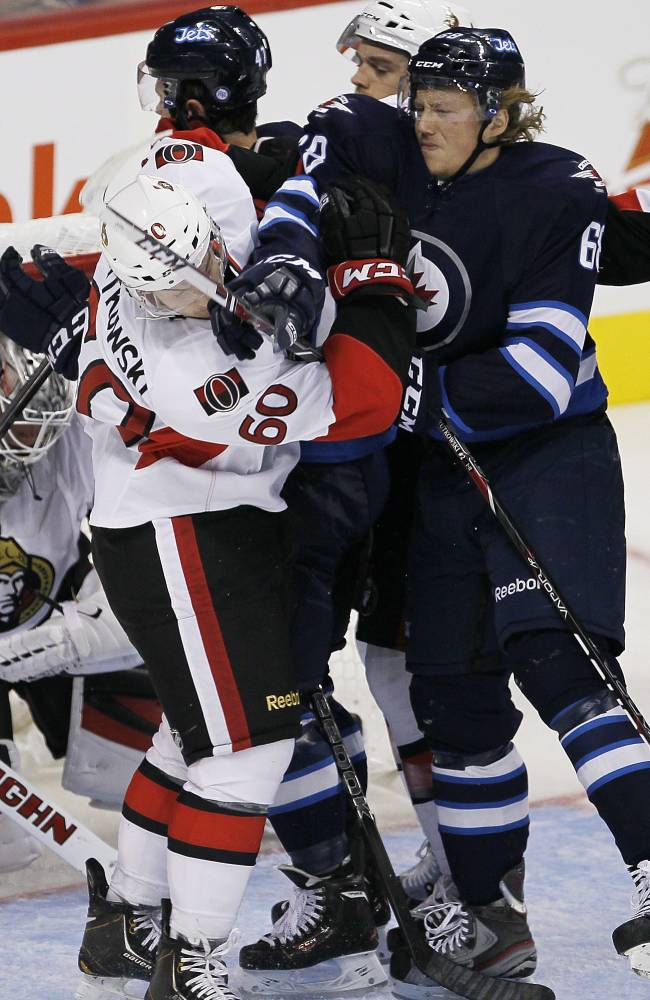 Winnipeg Jets' Ryan Olsen (68) and Ottawa Senators' Troy Rutkowski (60) fight for position in front of Senators goaltender Robin Lehner (40) during the first period of a preseason NHL hockey game in Winnipeg on Sunday, Sept. 15, 2013