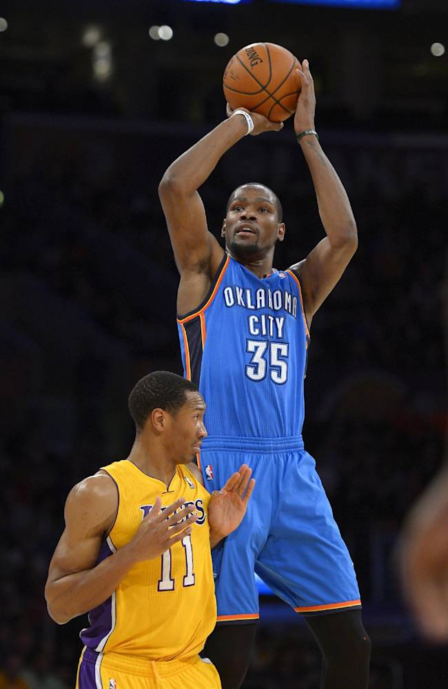 Oklahoma City Thunder small forward Kevin Durant, top, puts up a shot as Los Angeles Lakers small forward Wesley Johnson defends during the second half of an NBA basketball game, Thursday, Feb. 13, 2014, in Los Angeles