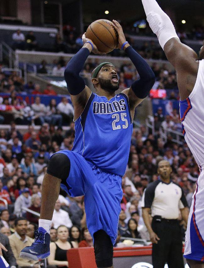 Dallas Mavericks' Vince Carter, center, looks to shoot as he is defended by Los Angeles Clippers' Glen Davis during the second half of an NBA basketball game on Thursday, April 3, 2014, in Los Angeles. The Mavericks won 113-107