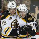 Boston Bruins' Reilly Smith, left, celebrates his game-winning goal with teammate Ryan Spooner during third period NHL hockey action against the Calgary Flames in Calgary, Alberta., Tuesday, Dec. 10, 2013. The Boston Bruins beat the Calgary Flames 2-1. (AP Photo/The Canadian Press, Jeff McIntosh)