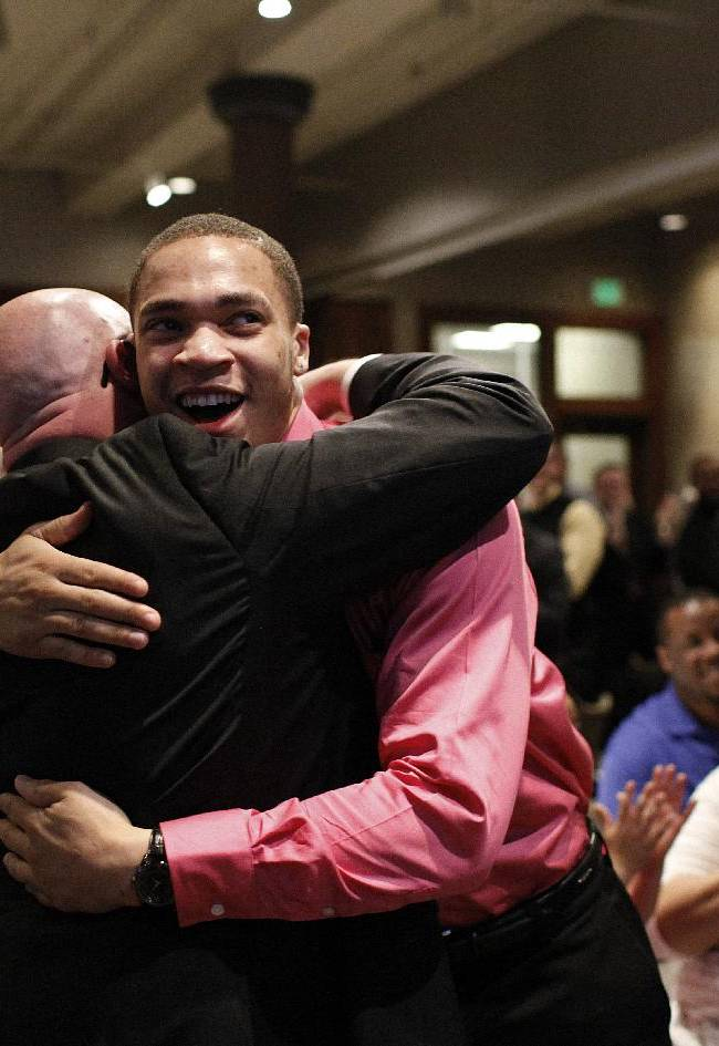 In this Sunday, March 16, 2014 photo, Western Michigan's senior guard David Brown hugs head coach Steve Hawkins, left, after the announcement of the school's NCAA college basketball tournament placement during Selection Sunday in Kalamazoo, Mich