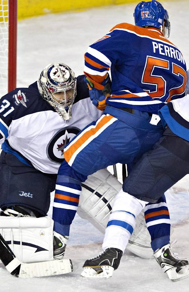 Winnipeg Jets goalie Ondrej Pavelec (31) tries to see past teammate Tobias Enstrom (39) and Edmonton Oilers' David Perron (57) as they battle in front of his net during third period NHL hockey action Tuesday, Oct. 1, 2013, in Edmonton, Alberta