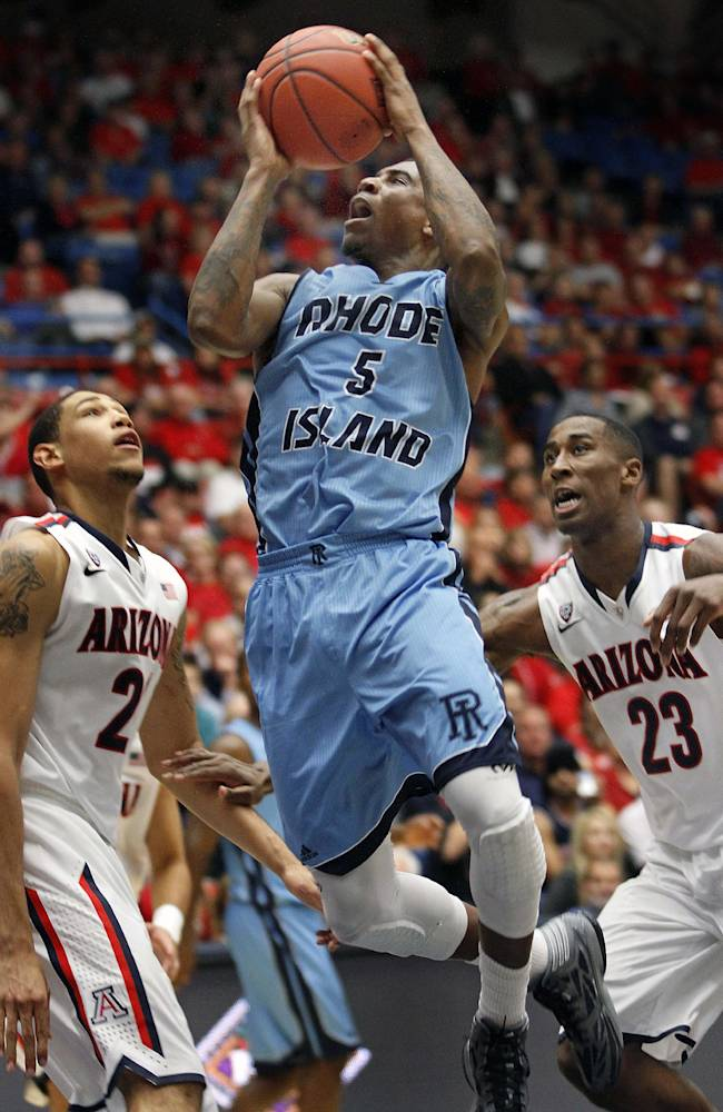 Rhode Island's Xavier Munford (5) shoots for two between Arizona's Brandon Ashley, left, and Rondae Hollis-Jefferson (23) in the second half of an college NCAA basketball game, Tuesday, Nov. 19, 2013 in Tucson, Ariz. This is in the second round of the NIT. Arizona won 87 - 59