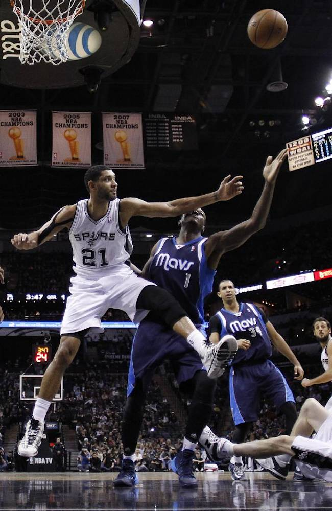 San Antonio Spurs' Tim Duncan (21) and Dallas Mavericks' Samuel Dalembert (1) reach for a rebound during the first half on an NBA basketball game, Wednesday, Jan. 8, 2014, in San Antonio