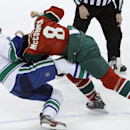 Vancouver Canucks left wing Tom Sestito, left, and Minnesota Wild center Cody McCormick (8) fall to the ice as they fight during the first period of an NHL hockey game in St. Paul, Minn., Wednesday, March 26, 2014. Both players received major penalties fo