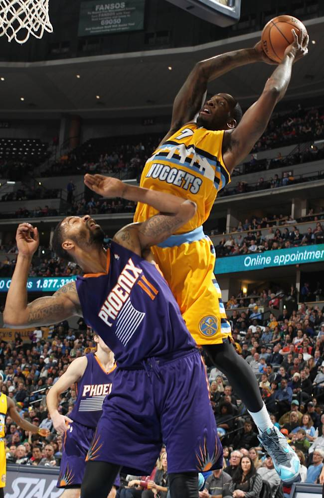 Denver Nuggets forward J.J. Hickson, right, goes up for a shot over Phoenix Suns forward Markieff Morris in the fourth quarter of the Suns' 103-99 victory in an NBA basketball game in Denver on Friday, Dec. 20, 2013