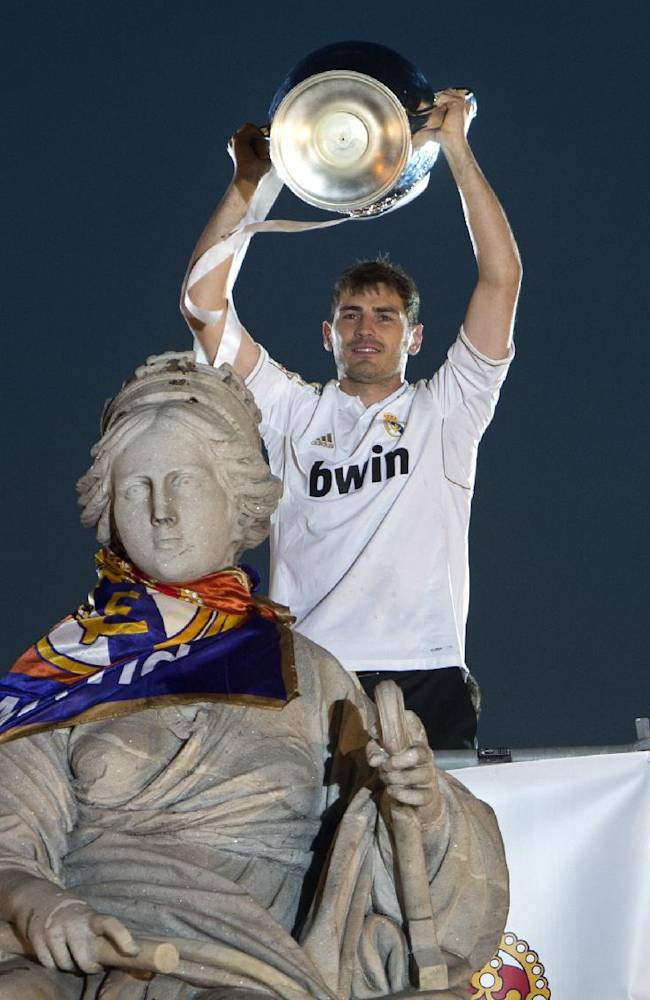 Real Madrid's goalkeeper Iker Casillas lifts the trophy next to the Cibeles statue in Madrid, Spain, Sunday, May 25, 2014, after the team won the Champions League final soccer match in Lisbon, Portugal by beating Atletico Madrid