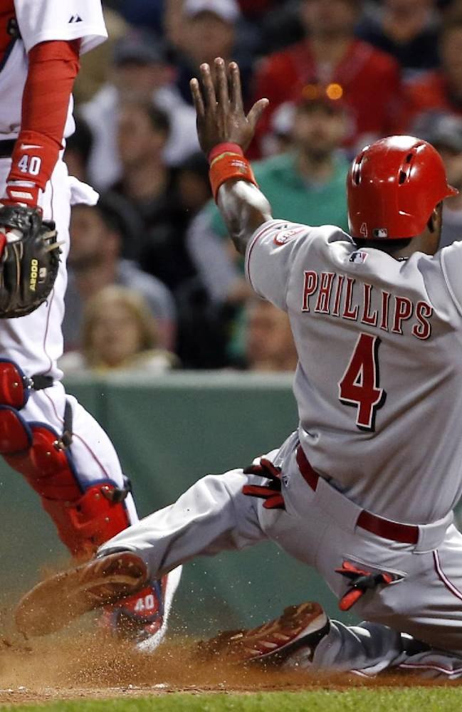 Cincinnati Reds' Brandon Phillips (4) slides into home to score on Ryan Ludwick's sacrifice fly as Boston Red Sox catcher A.J. Pierzynski (40) stands by during the eighth inning of a baseball game at Fenway Park in Boston, Tuesday, May 6, 2014