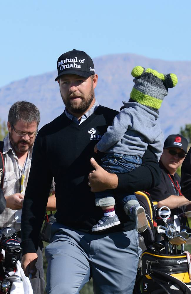 In this photo provided by the Las Vegas News Bureau, defending champion Ryan Moore walks to the first tee while carrying his son Tucker during the pro-am of the Shriners Hospitals for Children Open golf tournamentat TPC Summerlin in Las Vegas on Wednesday, Oct. 16, 2013