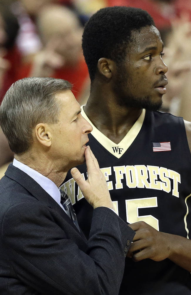 Wake Forest's Arnaud Adala Moto speaks with coach Jeff Bzdelik during the second half of an NCAA college basketball game in Raleigh, N.C., Tuesday, Feb. 11, 2014. North Carolina State won 82-67