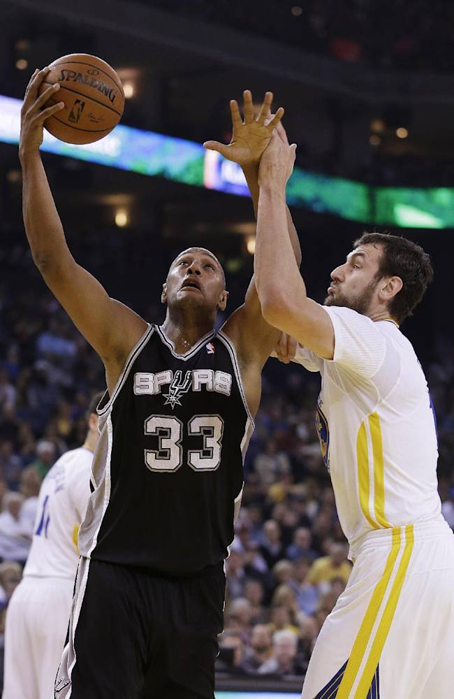 San Antonio Spurs forward Boris Diaw, left, goes to the basket against Golden State Warriors center Andrew Bogut, right, during the first quarter of their NBA basketball game Saturday, March 22, 2014, in Oakland, Calif